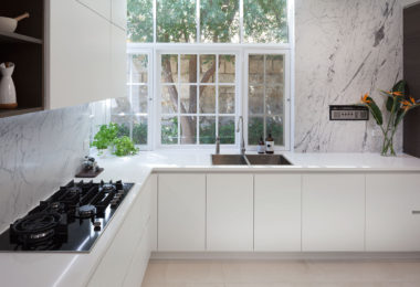 A renovated kitchen featuring white cabinetry with oak highlights, coupled with natural marble